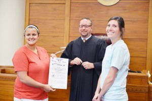 """Brides Holly Pryor, 23, of Nederland, left, and Tia Marshall, 25, of Nederland celebrate their nuptials in the Jefferson County Sub-Courthouse in Port Arthur Monday afternoon after Judge Marc DeRouen, Justice of the Peace for Precinct 2, married the """"partners in life and presented them to the courtroom as """"the Marshalls."""" The Marshalls, who live in Port Neches and have been together four years, are the first couple in the Lesbian, Gay, Bisexual and Transgender community to be married in Jefferson County. They were the first to fill out their marriage license application at the Jefferson County Courthouse in Beaumont Monday morning, arriving to sign their paperwork an hour and a half after the county began issuing same-sex marriage license applications."""