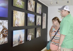 Emily Daniel and Adam Handly look at their engagement photo, taken on the beach in Galveston, during the ribbon cutting for Everlasting Images Photography and Video, 4300 Lincoln Ave., Suite 4 in Groves, on Thursday.