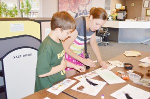 """Nederland native Jennifer Weeren, right, helps her nephew Connor Blackwell, 8, complete a feathers, scales and fur craft during the """"Super Sleuths"""" children's program at the Museum of the Gulf Coast in Port Arthur Tuesday."""