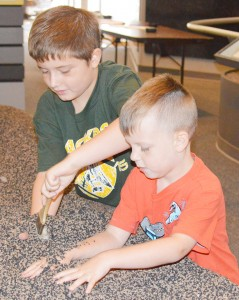 """Cousins Connor Blackwell, 8, left, and Max Weeren, 5, of Nederland explore a hands-on exhibit during the """"Super Sleuths"""" children's program at the Museum of the Gulf Coast in Port Arthur Tuesday."""