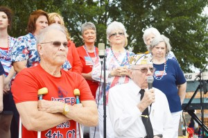 "Nederland Mayor Richard ""Dick"" Nugent, left, and musical performers Sweet Adelines get ready to surprise the Fireworks Extravaganza Fourth of July celebration's guest of honor, Rt. U.S. Army Major James White, right, for the WWII veteran's 90th birthday at Doornbos Heritage Park in Nederland Saturday."