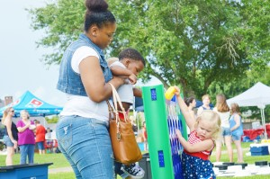 Naisihia Williams, of Port Arthur, left, helps her 2-year-old son Deezy Givens play an oversized game of Connect 4 with Dallas native Anna Terry, 2, during the Fireworks Extravaganza Fourth of July celebration at Doornbos Heritage Park in Nederland Saturday.