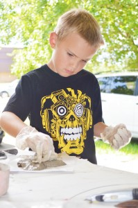 Ian Koushan, 8, of Bridge City decorates his freeform concrete cross with sea glass during the annual Art Smart kids' summer camp at the Texas Artists Museum in Port Arthur Tuesday.