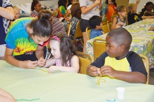 """Volunteer Jamye Nchugh, left, shows Art Smart 2015 students Hollierose Justice, 5, of Groves and Bryson Greene, 6, of Port Arthur how to make a """"bead puppy"""" at the Texas Artists Museum in Port Arthur Tuesday."""