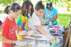 """Art Smart 2015 students decorate their freeform concrete designs with sea glass and sea shells to match the theme of the week, """"It's a Shore Thing,"""" at the Texas Artists Museum in Port Arthur Tuesday."""