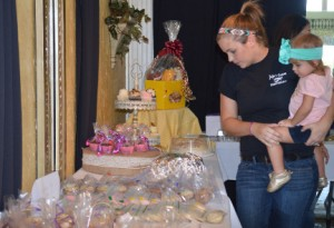Bethany Davis, left, and her daughter Presley, 2, looks at items at a bake sale to benefit Austyn Halter at Beau Reve on Saturday. Mary Meaux/The News