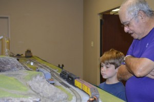 Nolan Pipton, 8, left, and his grandfather Cruz Maciel watch model trains roll by during Model Trains in (Loco)motion at Thursday at Effie and Wilton Public Library in Port Neches on Thursday. Mary Meaux/The News