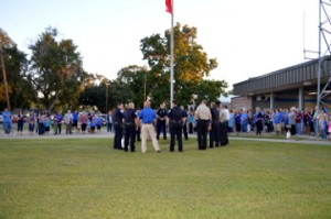 Port Neches Police officers surround the flagpole at the vacant fire station while surrounded by community members during See You At the Station on Wednesday. Mary Meaux/The News