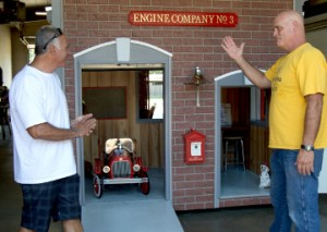 Port Arthur Fire Engineer Mike Perez, left, and Captain Gerrit Achord stand in front of a playhouse built by firefighters for Casas for CASA fundraiser. Mary Meaux/The News