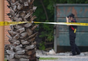 A police department official takes photographs during a murder investigation in the 4200 block of Gulfway Drive on Tuesday.   Mary Meaux/The News