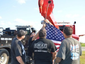 Tow truck drivers with SWAT and Brian's Wrecker Service hoist a U.S. flag on one of SWAT's trucks before the Slow Down and Move Over awareness event along Texas 73 near Taylor Bayou Bridge on Wednesday. Mary Meaux/The News