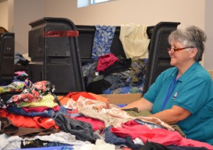 Goodwill employee Margaret Hebert sorts through bins of clothing in the back room at the newly opened Goodwill, 4352 FM 365, on Friday. Mary Meaux/The News