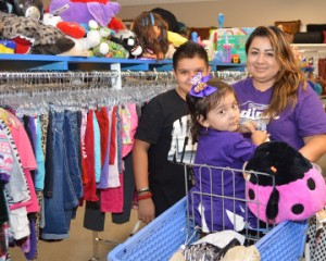 Martha Rodriguez, right, shops with children Mia, 2, and Edward, 12, during the grand opening of Goodwill, 4352 FM 365, on Friday. Mary Meaux/The News