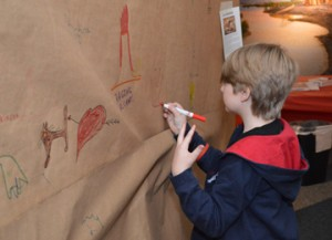 Lucas Howard, 7, of Nederland, traces his handprint onto paper while learning about cave drawings during a free family day at the Museum of the Gulf Coast on Saturday. Children and families learned about archeology and performed paleontology digs during the event.  Mary Meaux/The News