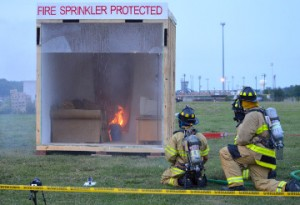 Port Neches firefighters stand guard as a fire is doused by a fire sprinkler system during a live burn demonstration at the department's open house on Thursday. The sprinkler activated after about one minute into the blaze thus saving a majority of the room. Mary Meaux/The News