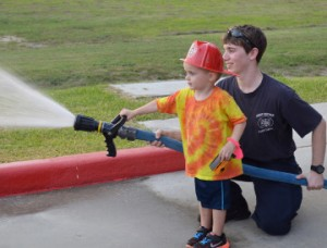 Bryce Brentlinger, 3, of Port Neches, uses afire hose with the assistance of Port Neches Firefighter John Brown during the fire department's open house on Thursday. Mary Meaux/The News