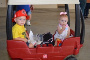 James Stewart, 2, left, and sister Jonni Sue Stewart, 1, of Groves, share a wagon during the Port Neches Fire Department's open house on Thursday. Mary Meaux/The News