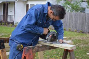 Texas Gas Service employee Shannon O'Connor saws wood for a wheelchair ramp to benefit a Groves couple on Thursday. Mary Meaux/The News