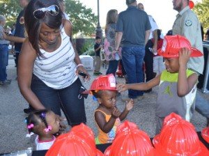 "Robert Johnson, 6, right, places a fire hat on his sister Raven Jones, 2, and little sister Holly Oville, 1, and mother Dominque Jones look on during a Port Arthur fire prevention week event at the Robert A. ""Bob"" Bowers Civic Center on Monday. Mary Meaux/The News"