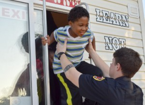 "Andrew Jackson, 7, left, emerges from the Bridge City Fire Department Children's Fire Safety House with the assistance of Port Arthur Firefighter Tyler Barbay during a Port Arthur fire prevention week event at the Robert A. ""Bob"" Bowers Civic Center on Monday. Mary Meaux/The News"
