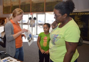 Museum of the Gulf Coast Education Coordinator Stephanie Harren, left, tells Crystal Coleman, right, and Salem Coleman, about the Free Family Fun Day events where children learned about archeology and paleontology Saturday. Mary Meaux/The News