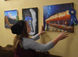 Alivia McClain, 11, adjusts her first place and Robert Pastorella Sr. Memorial Award winning painting on Monday at Groves Café and Coffee Bar. Mary Meaux/The News