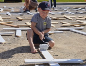 Caden Mercer, 3 ½, paints a cross outside Summer's Abbey Flooring in Port Neches on Tuesday