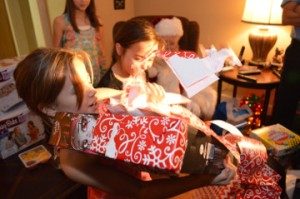 Cadence Clark, left, unwraps an early Christmas gift at her grandparent's home in Beauxart Gardens Wednesday night. Mary Meaux/The News