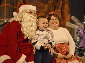 Austin Carter, 4, visits with Mr. and Mrs. Santa Claus during Christmas events at Celebration Park in Groves on Friday. Marty Meaux/The News