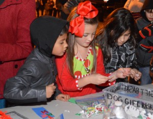 Matthew Tipton, 5, left, Olivia Mitchell, 6, and Sally Robles, 8, make holiday decorations during An Old Fashioned Christmas in Groves on Lincoln Avenue on Friday. Mary Meaux/The News