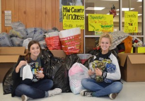 Nederland High School students Kendal DeVillier, left, and Taylor Desormeaux show some of the items collected during Mid-County Kindness to benefit the Hospitality Center in Port Arthur. Mary Meaux/The News
