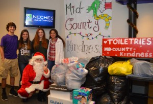 Port Neches-Groves High School students Tyler Pippin, left, Mackinley Brown, Rachel Hammersmith, and Maria Salazar pose with Santa Claus, also known as Madison Hamby with items collected during Mid-County Kindness to benefit the Hospitality Center in Port Arthur. Mary Meaux/The News