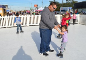 """Charles Meaux Jr. helps his daughter, Josette """"Josie"""" Meaux, 2 1/2, """"ice"""" skate during Christmas on the Avenue in Nederland on Saturday. Mary Meaux/The News"""