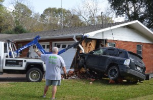 A tow truck driver removes a vehicle from a home in the 2800 block of Eighth Street in Port Neches shortly before noon Wednesday. Mary Meaux/The News