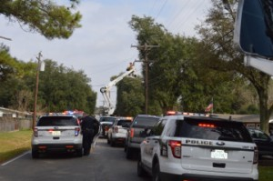 First responders lined the street as Entergy employees remove a live wire from a home after a vehicle crashed through a garage home in the 2800 block of Eighth Street in Port Neches shortly before noon Wednesday. Mary Meaux/The News
