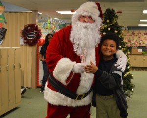Santa Claus poses for a photo with Dowling Elementary School student Rylan Johnson during Y Reads With You, Literacy Program with the help of Flint Hills Resources Port Arthur volunteers on Wednesday. Mary Meaux/The News