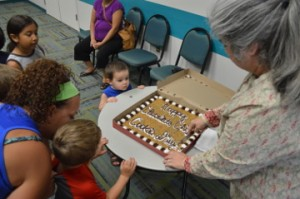 Michael Toon, top, watches as Librarian Molli Hall cuts a piece of cookie cake during an early celebration of National Chocolate Chip Cookie Day at the Marion and Ed Hughes Public Library in Nederland on Wednesday. Mary Meaux/The News