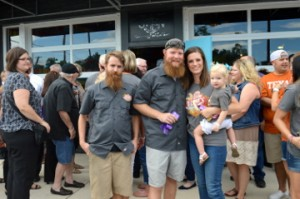 Neches Brewing Company co-owner David Pool, left, stands with fellow co-owner Tyler Blount, his wife Brittani and daughter Logan after a ribbon cutting for the brewpub on Thursday. Mary Meaux/The News