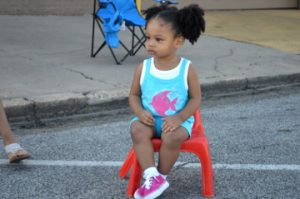 Zoey Young takes a seat as she waits for the annual cavOILcade parade to begin in Port Arthur on Saturday. Mary Meaux/The News