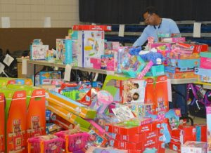 """Port Arthur Police Officer Nathan Mingo sorts through toys during the Blue Santa program at the Robert A. """"Bob"""" Bowers Civic Center on Friday. Mary meaux/The News"""