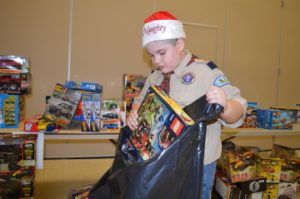 """Boy Scout Antonio Ortiz, 10, places toys in bags during the Port Arthur Police's Blue Santa program at the Robert A. """"Bob"""" Bowers Civic Center on Friday. Mary Meaux/The News"""