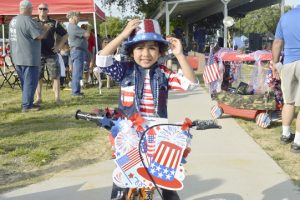 Aaron Jasani, 3, stops for a photo after the Bike and Wagon Parade at Doorknobs Park for the Nederland Fourth of July. (Mary Meaux/The News)