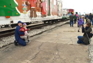 U.S. Coast Guard LTJG Matt Lemanski and his children Leo and Julia pose for a photo next to the KCS Holiday Express train as his wife Jelsea snaps photos on Thursday. Mary Meaux/The News