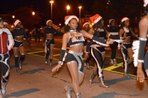 Dancers with Santa caps strut during the Port Arthur's Annual Cultural Lighted Christmas Parade on Procter Street on Friday. Mary Meaux/The News