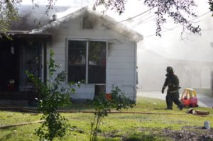 A Port Arthur Firefighter walks past a child's toy while working to extinguish a house fire in the 3000 block of 26th Street on Thursday. Mary Meaux/The News