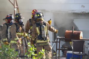 Port Arthur firefighters map out a plan to extinguish a fire at a home in the 3000 block of 26th Street on Thursday. Mary Meaux/The News