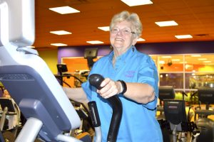 Nellie McCoy, 68, works out on an elliptical machine in the cardio section at Exygon Health and Fitness Club in Nederland. (Lorenzo Salinas/The News)