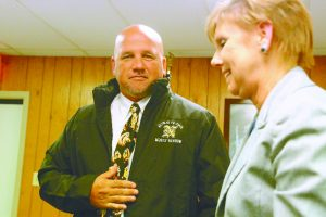 Nederland ISD Superintendent Robin Perez presents Monte Barrow with a jacket during his introduction as head football coach and athletic director Monday. (I.C. Murrell/The News)