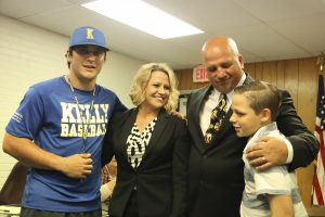 New Nederland head football coach and athletic director Monte Barrow receives congratulations from, from left, son Seth, 22, wife Amber and son Reeve, 12, during his introduction at Monday's school board meeting. (I.C. Murrell/The News)