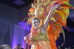 Leslie Ruiz, dressed as Goddess of the Sun, throws out beads to Aurora attendees. (Lorenzo Salinas/The News)